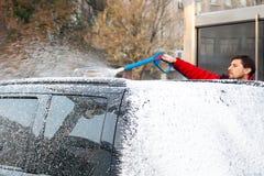 Un hombre en cubiertas de una chaqueta rojas un coche negro con espuma en un t?nel de lavado del autoservicio imágenes de archivo libres de regalías