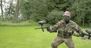 Un hombre en el equipo rosado que lleva a cabo dos la odisea 7Q de los armas 4K FS700 de Paintball metrajes
