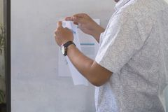 Un hombre en el paño blanco que prepara el papel con la cinta lista para la presentación foto de archivo
