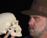 Un hombre en Fedora examina un cráneo Imagenes de archivo