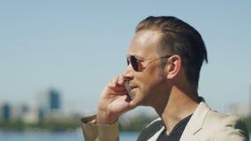 Un hombre en gafas de sol que habla con alguien emocionado en el teléfono almacen de video