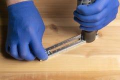 Un hombre en guantes azules está cortando un agujero en una hoja de la madera contrachapada foto de archivo