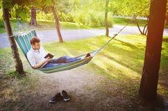 Un hombre en hamaca lee un libro Imagen de archivo