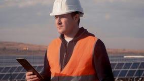 Un hombre en un ingeniero del casco en el fondo de una planta de energía solar que sostiene una tableta digital metrajes