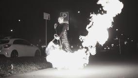 Un hombre en la calle vierte el fuego de un lanzallamas en diversas direcciones Plan fresco en la cámara lenta metrajes