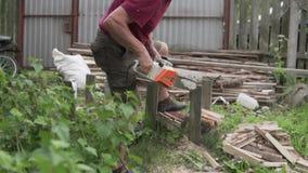 Un hombre en la madera que asierra de la cabaña con una sierra eléctrica almacen de video
