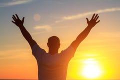 Un hombre en la playa en la puesta del sol muestra a sus manos cómo es feliz él está con el concepto de viaje y de relajación fotos de archivo libres de regalías