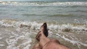Un hombre en la playa que toma el sol en la resaca disfruta del sonido del océano y de las ondas de balanceo en la playa arenosa metrajes