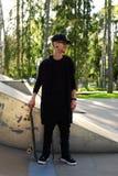 Un hombre en la ropa negra que presenta con el monopatín Imágenes de archivo libres de regalías