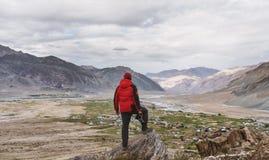 Un hombre en la situación roja de la chaqueta en cumbre de la montaña, y Mountain View Forma de vida del viaje, aventurero, éxito fotos de archivo