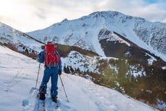 Un hombre en las montañas Esquí que viaja en una snowboard partida Un hombre se coloca con el suyo de nuevo al espectador y a las fotos de archivo