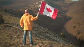 Un hombre en las monta?as coloca y sostiene la bandera canadiense ?l est? llevando la ropa y los vidrios amarillos brillantes metrajes