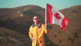 Un hombre en las monta?as coloca y sostiene la bandera canadiense ?l est? llevando la ropa y los vidrios amarillos brillantes almacen de metraje de vídeo