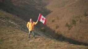 Un hombre en las monta?as coloca y sostiene la bandera canadiense ?l est? llevando la ropa y los vidrios amarillos brillantes almacen de video