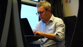 Un hombre en letras que mecanografían de un ordenador portátil almacen de metraje de vídeo