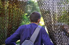 Un hombre en un parque zool?gico entra en una jaula al aire libre a los p?jaros a trav?s imagen de archivo libre de regalías