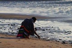 Un hombre en rodilla doblada en la playa Imagenes de archivo