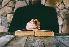 Un hombre en ropa negra con las gotas de un rezo a disposición que ruega delante de un libro abierto viejo Fotos de archivo