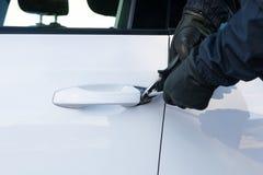 Un hombre en ropa negra está intentando romper la cerradura de la puerta de coche delante del secuestro fotos de archivo libres de regalías