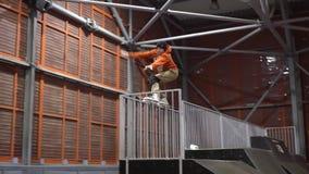 Un hombre en saltos de los rodillos en la verja en la rampa salta abajo, cámara lenta almacen de metraje de vídeo