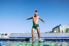 Un hombre en Santa Claus Cap salta en una piscina en un resor tropical Imagen de archivo libre de regalías