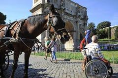 Un hombre en silla de ruedas que disfruta al aire libre de las vacaciones romanas En el fondo el arco de imagenes de archivo