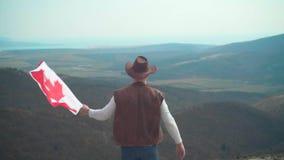 Un hombre en un sombrero, un chaleco y una chaqueta de cuero y vaqueros sostiene una bandera canadiense r almacen de metraje de vídeo