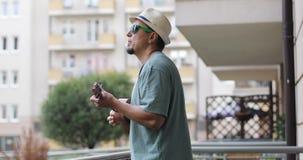 Un hombre en un sombrero con una barba juega el ukelele en el balcón en el verano metrajes