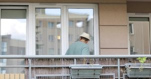 Un hombre en un sombrero con una barba sale sobre el balcón y los juegos en el ukelele almacen de video