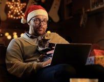 Un hombre en sombrero del Año Nuevo del ` s de Papá Noel celebra un gato y el trabajo con el ordenador portátil Fotos de archivo