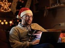 Un hombre en sombrero del Año Nuevo del ` s de Papá Noel celebra un gato y el trabajo con el ordenador portátil Imagen de archivo