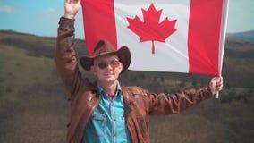 Un hombre en un sombrero y gafas de sol, chaqueta de cuero y vaqueros sosteniendo una bandera canadiense almacen de video