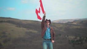 Un hombre en un sombrero y gafas de sol, chaqueta de cuero y vaqueros sosteniendo una bandera canadiense almacen de metraje de vídeo