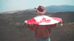 Un hombre en un sombrero y gafas de sol, una chaqueta de cuero y los vaqueros lanz? una bandera canadiense en el suyo detr metrajes