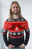 Un hombre en un suéter del ` s del Año Nuevo con un ornamento de los ciervos Imagen de archivo libre de regalías