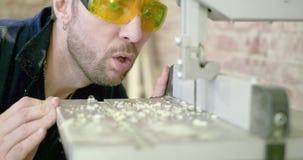 Un hombre en un taller de la carpintería que lleva los vidrios protectores limpia al tablero blowing almacen de video