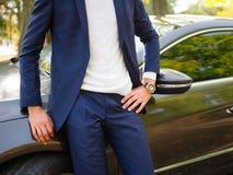 Un hombre en un traje azul, un golf blanco y un reloj en su mano está colocando t cerca del coche afuera fotografía de archivo