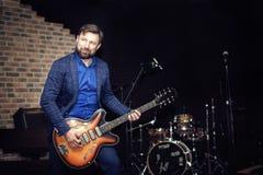 Un hombre en un traje azul toca la guitarra imágenes de archivo libres de regalías