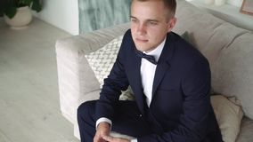 Un hombre en un traje de negocios azul que se sienta en el sofá almacen de metraje de vídeo