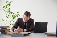 Un hombre en un traje de negocios trabaja en un escritorio con un ordenador y los libros en la oficina imagen de archivo