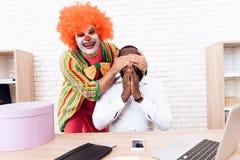 Un hombre en un traje del payaso cierra ojos a un hombre negro que se siente en su escritorio Fotografía de archivo libre de regalías
