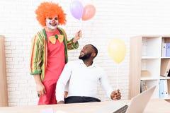 Un hombre en un traje del payaso se está colocando al lado de un hombre negro que se siente en su escritorio Foto de archivo