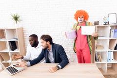 Un hombre en un traje del payaso se está colocando al lado de otros hombres en una oficina de negocios brillante el día del ` de  Imagen de archivo
