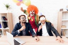 Un hombre en un traje del payaso se está colocando al lado de otros hombres en una oficina de negocios brillante el día del ` de  Imágenes de archivo libres de regalías