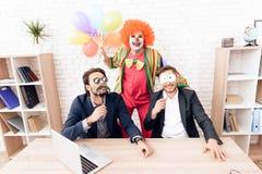 Un hombre en un traje del payaso se está colocando al lado de otros hombres en una oficina de negocios brillante el día del ` de  Foto de archivo libre de regalías
