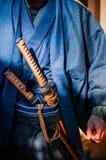 Un hombre en traje del samurai con la espada de Katana Imagen de archivo libre de regalías