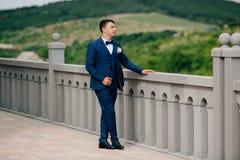Un hombre en un traje elegante da un paseo a lo largo de la plataforma de la visión y disfruta del buen tiempo en su día de boda Foto de archivo