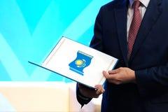 Un hombre en un traje oscuro sostiene una carpeta abierta con la imagen de la bandera nacional de la República de Kazajistán El c fotos de archivo