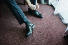 Un hombre en un traje pone los zapatos en sus pies foto de archivo libre de regalías
