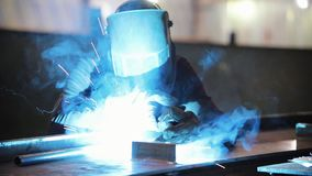 Un hombre en un traje protector trabaja con una soldadora Luz brillante metrajes